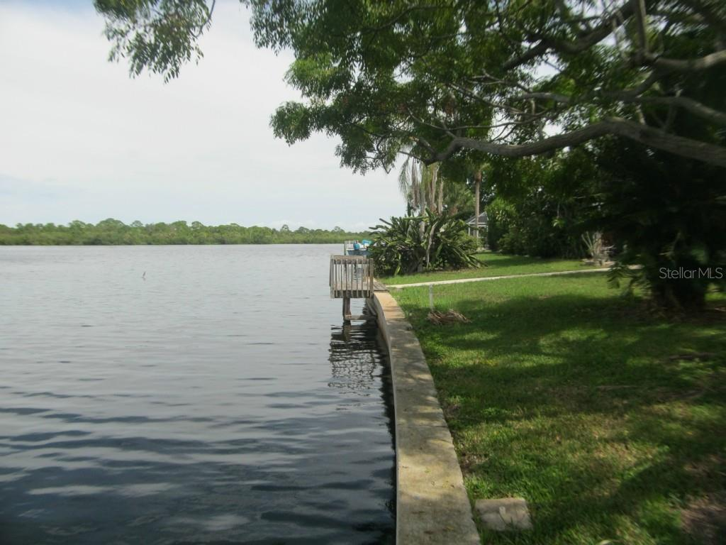 This view along the seawall is taken from the north end of the lot looking along the lot to the south.  The small fishing dock is about center of the lot. - Single Family Home for sale at 450 Coral Creek Dr, Placida, FL 33946 - MLS Number is D5901346