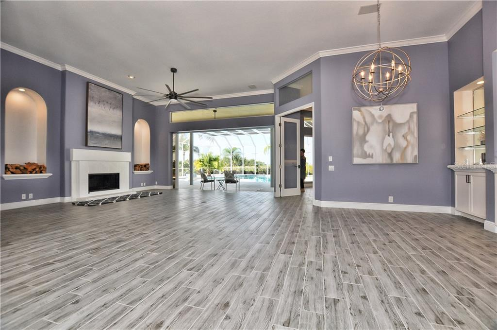 this formal living room has a fireplace with sliders that open into the pool area overlooking the Myakka River. The French doors open into the new remodeled kitchen - Single Family Home for sale at 3121 Rivershore Ln, Port Charlotte, FL 33953 - MLS Number is D5917816