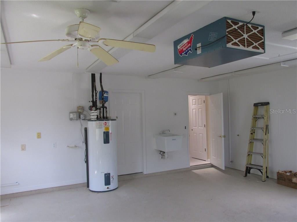 This is a partial view of the work shop or cart garage.  The door leads to the utility area where the washer and dryer will be located.  There is attic storage above this area with pull down stairs.  The breaker panels are located in this room and a sub panel for a generator is in place.  There is an 8 or 9 foot garage door with automatic opener in this room for the golf cart or moving any big projects around. - Single Family Home for sale at 3001 Rivershore Ln, Port Charlotte, FL 33953 - MLS Number is D5917929