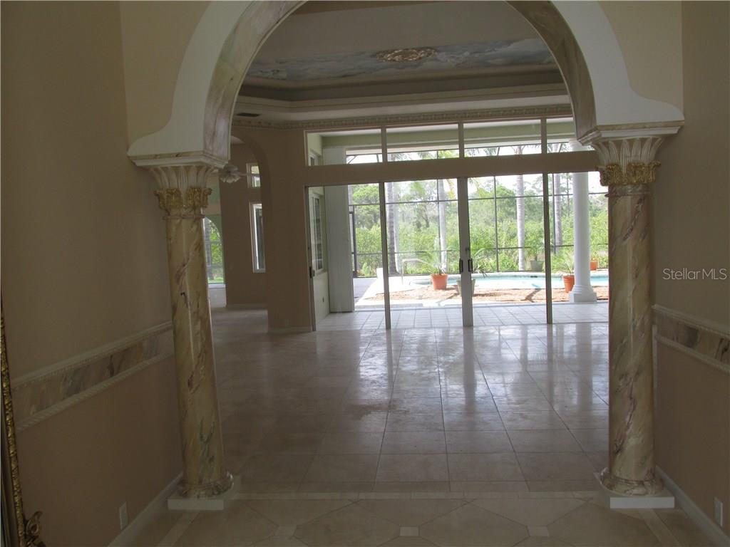 This is the view from the foyer.  To the left is a mirror over 8 feet tall that is included in the sale.   The columns feature faux marble painting that compliments the chair rail and trim.  It looks into the formal living room and thru the sliding glass doors into the pool area. - Single Family Home for sale at 3001 Rivershore Ln, Port Charlotte, FL 33953 - MLS Number is D5917929