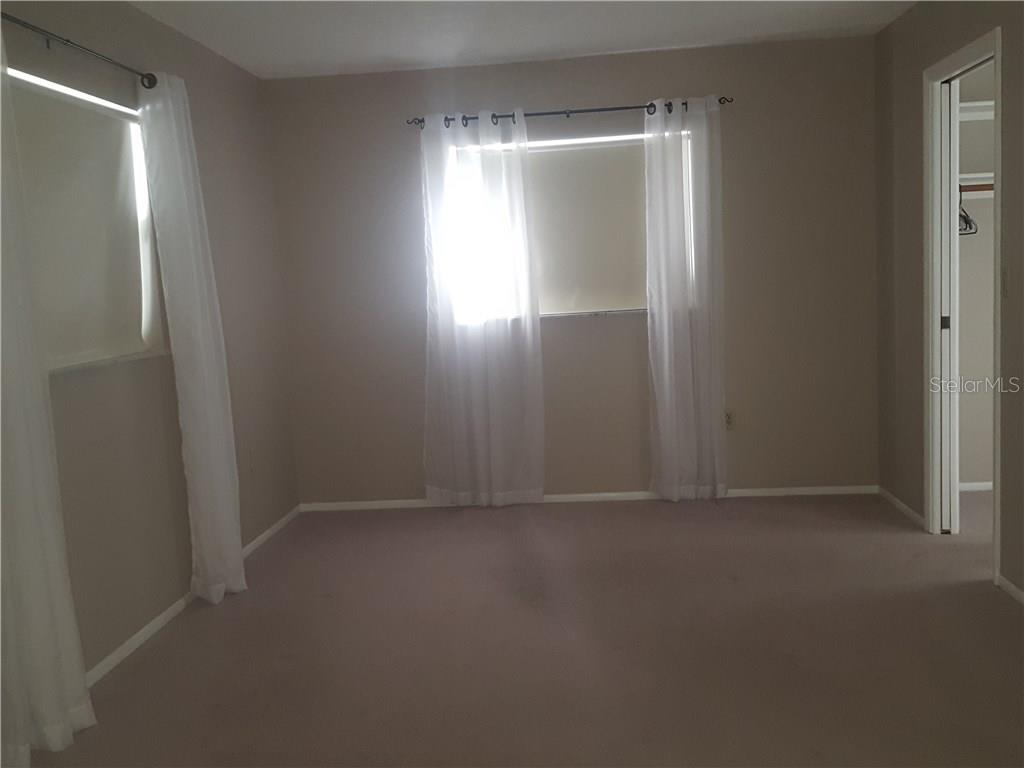 Master bedroom with the furniture gone.  This rooms open to the living area with sliding glass doors. - Single Family Home for sale at 21068 Halden Ave, Port Charlotte, FL 33952 - MLS Number is D5918749