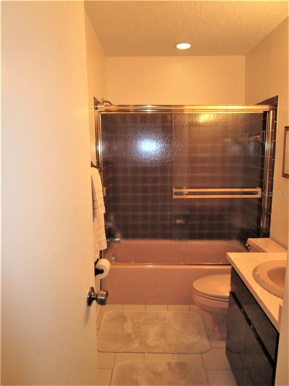 Guest bathroom has 2 piece vanity, combination tub/shower w/glass door & tiled flooring. - Condo for sale at 6796 Gasparilla Pines Blvd #14, Englewood, FL 34224 - MLS Number is D5919892