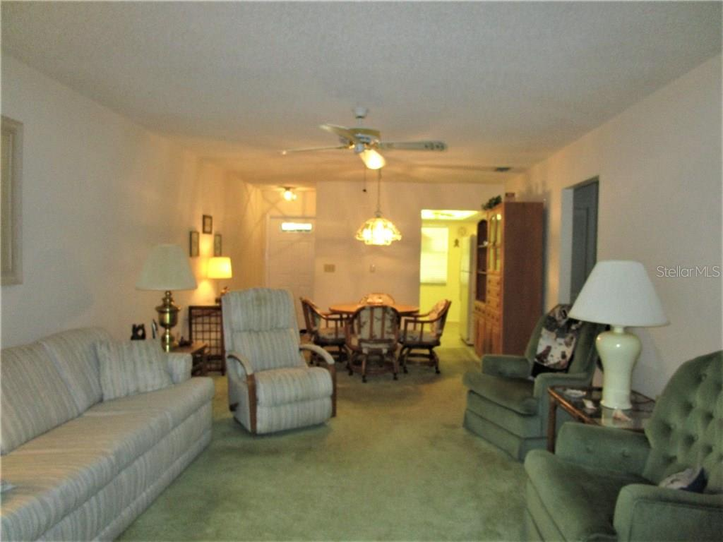 Living/Dining room combination has carpeted flooring & ceiling fan. - Condo for sale at 6796 Gasparilla Pines Blvd #14, Englewood, FL 34224 - MLS Number is D5919892