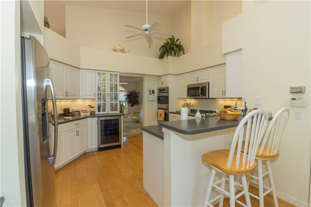 The kitchen features stainless appliances, solid surface counter tops, wine cooler and plenty of storage with a walk-in pantry. - Single Family Home for sale at 1439 Deer Creek Dr, Englewood, FL 34223 - MLS Number is D5921060
