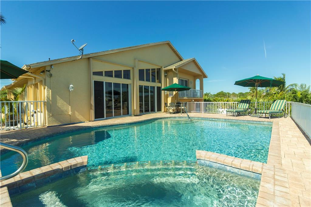 From this spa view, notice the balcony off the master bedroom beyond the pool.  The paver deck is large enough for umbrellas, tables and chairs with still plenty of walking-around room. - Single Family Home for sale at 1439 Deer Creek Dr, Englewood, FL 34223 - MLS Number is D5921060
