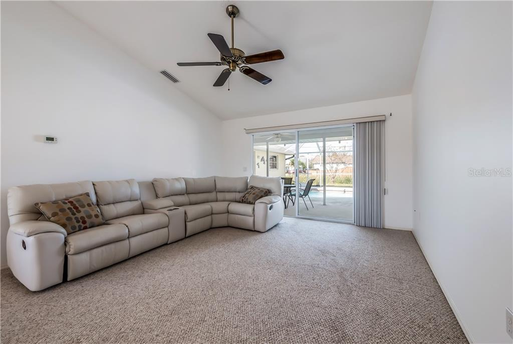 Large formal living room with sliding doors to the pool area. - Single Family Home for sale at 11010 Deerwood Ave, Englewood, FL 34224 - MLS Number is D5921766