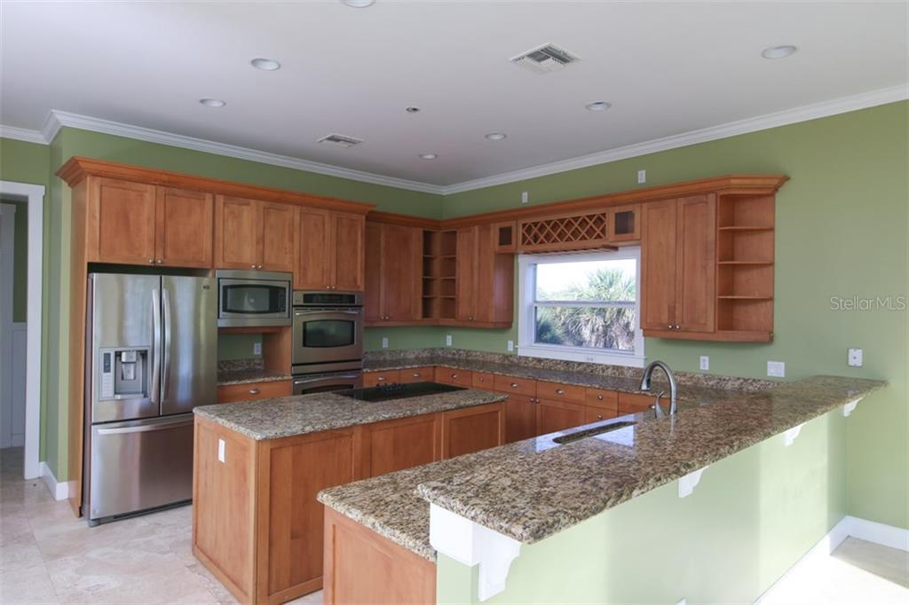 Kitchen with Wood Cabinets, Granite Countertops and Stainless Steel Appliances - Single Family Home for sale at 25 Palm Dr, Placida, FL 33946 - MLS Number is D5921936