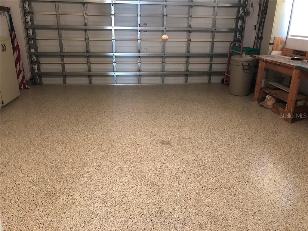 Textured and sealed garage floor for easy care. Garage also has a fully retractable screen door with a remote control too. - Villa for sale at 610 Linden Dr #349, Englewood, FL 34223 - MLS Number is D6100823