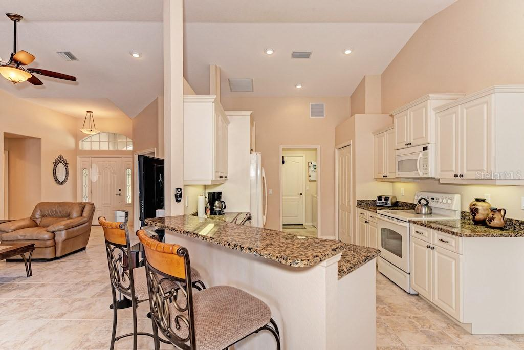 Breakfast bar, granite countertops, cabinets with crown molding and under cabinet lighting. - Single Family Home for sale at 7256 Holsum St, Englewood, FL 34224 - MLS Number is D6101787