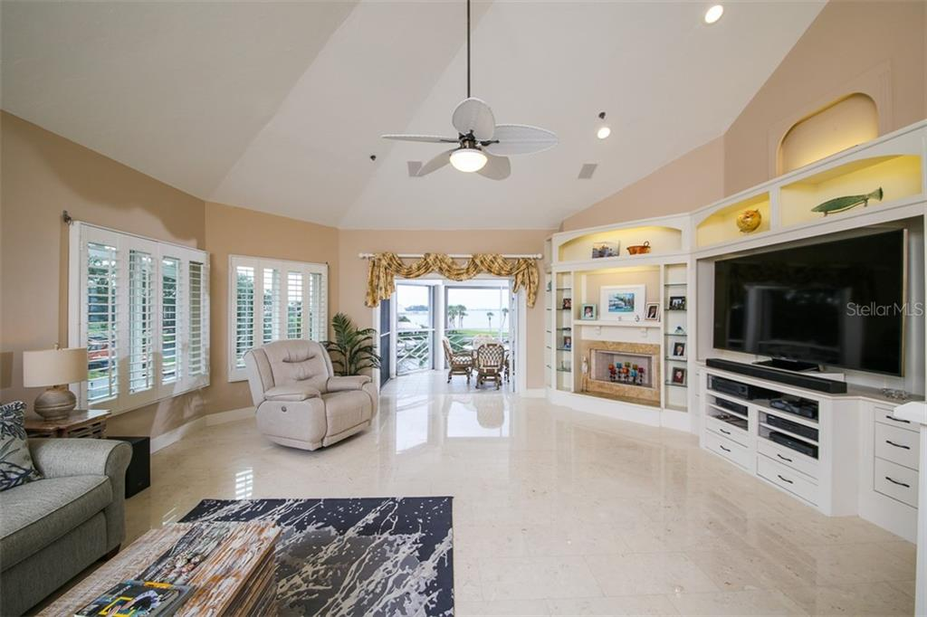 Living room with plantation shutters & built ins - Condo for sale at 11000 Placida Rd #2103, Placida, FL 33946 - MLS Number is D6102674
