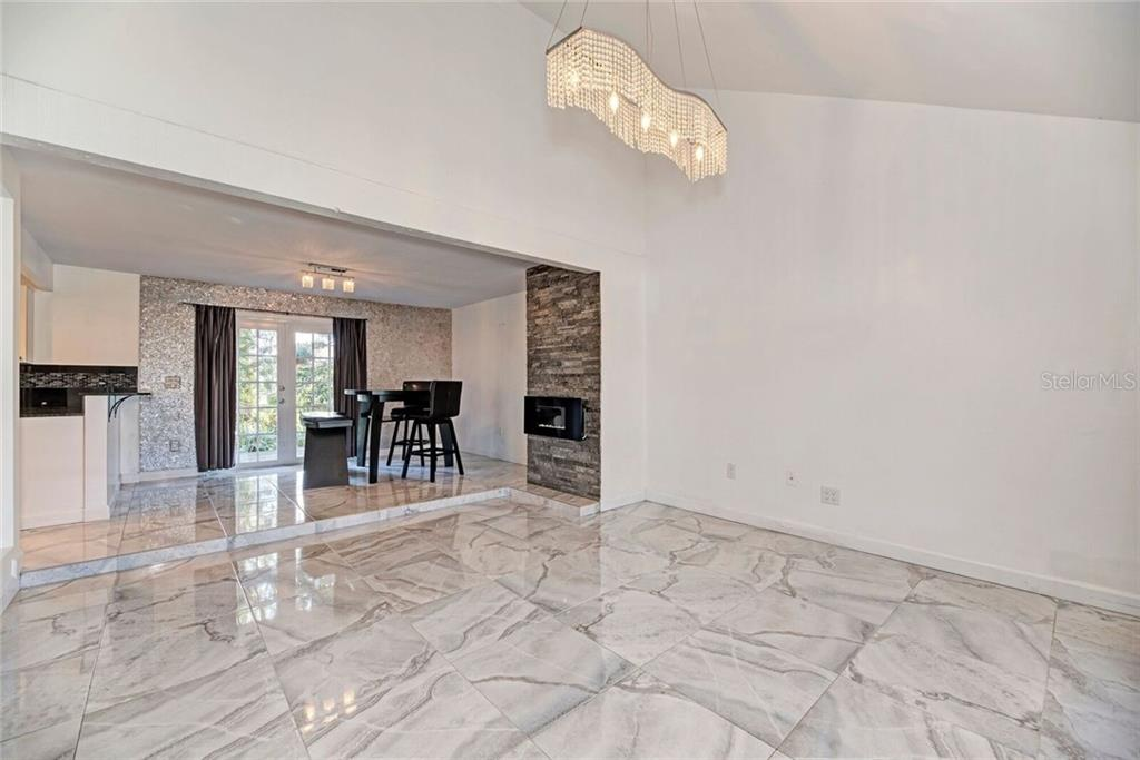 Great room with gorgeous flooring, electric fireplace, and updated lighting. - Single Family Home for sale at 3723 Shamrock Dr, Venice, FL 34293 - MLS Number is D6102893