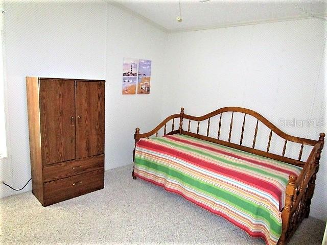 Guest bedroom has vaulted ceiling, ceiling fan, wall closet and Berber carpeted flooring. - Manufactured Home for sale at 1800 Englewood Rd #95, Englewood, FL 34223 - MLS Number is D6103776