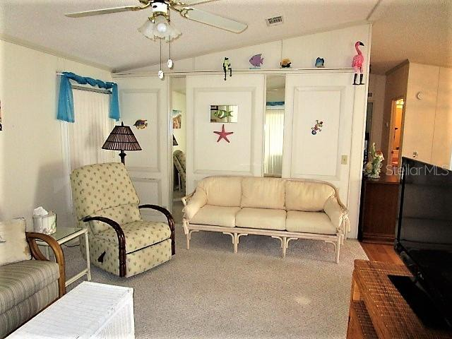 Living room has cathedral ceiling, ceiling fan and carpeted flooring. - Manufactured Home for sale at 1800 Englewood Rd #95, Englewood, FL 34223 - MLS Number is D6103776
