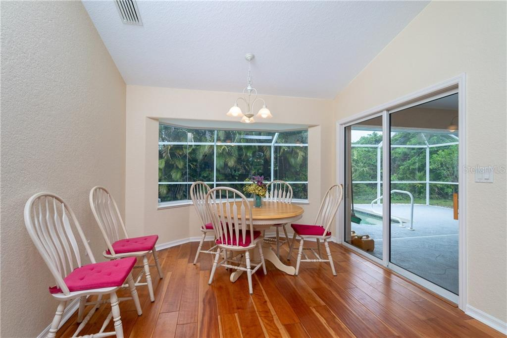 Breakfast nook has an aquarium window and sliding glass doors to Lanai and pool area. - Single Family Home for sale at 30 Medalist Way, Rotonda West, FL 33947 - MLS Number is D6106239