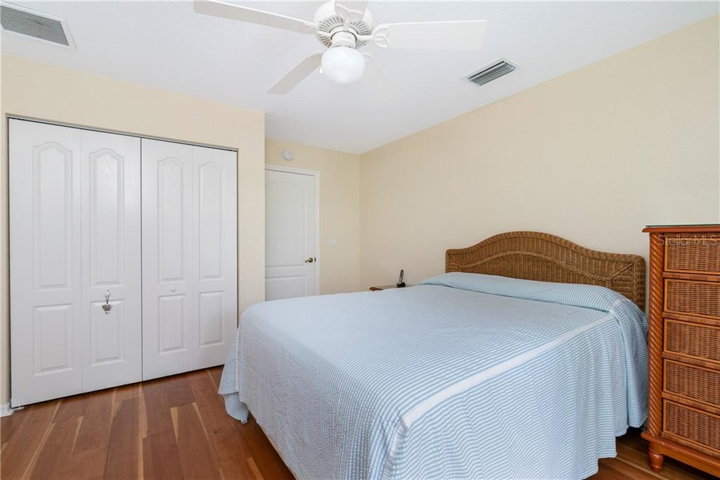 Guest bedroom 3 has ceiling fan, wall closet & sliding glass doors to Lanai. - Single Family Home for sale at 30 Medalist Way, Rotonda West, FL 33947 - MLS Number is D6106239