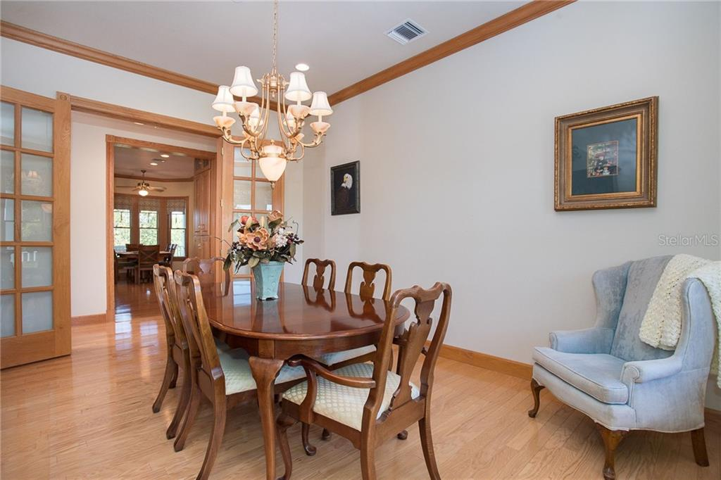 Formal dining room with custom window treatments, volume ceilings and more beautiful wood working. - Single Family Home for sale at 550 S Oxford Dr, Englewood, FL 34223 - MLS Number is D6111512