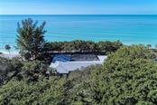 The native sea grapes offer protection from the salt spray. - Single Family Home for sale at 7400 Manasota Key Rd, Englewood, FL 34223 - MLS Number is D6104362
