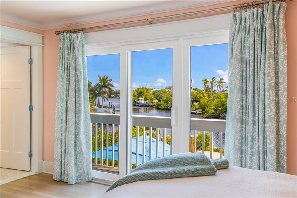 The main floor bedroom suite offers impact-glass sliding doors that access the balcony overlooking the canal, pool and spa - Single Family Home for sale at 511 Loquat Dr, Anna Maria, FL 34216 - MLS Number is T3196169