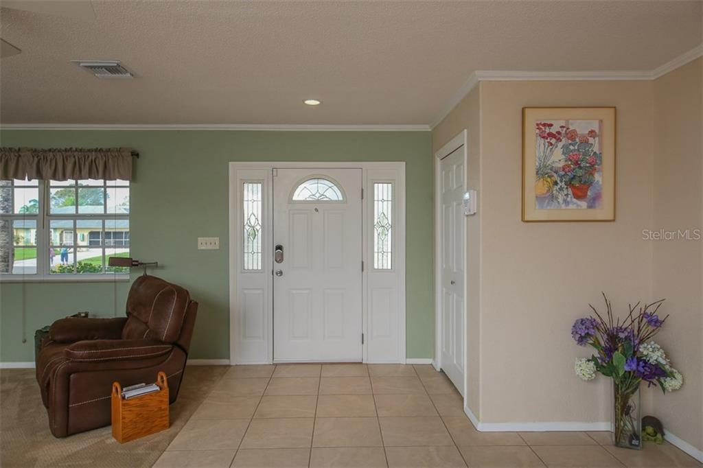 Entry foyer highlighted by leaded half round & side light windows & hall closet. - Single Family Home for sale at 2332 Mauritania Rd, Punta Gorda, FL 33983 - MLS Number is C7234250