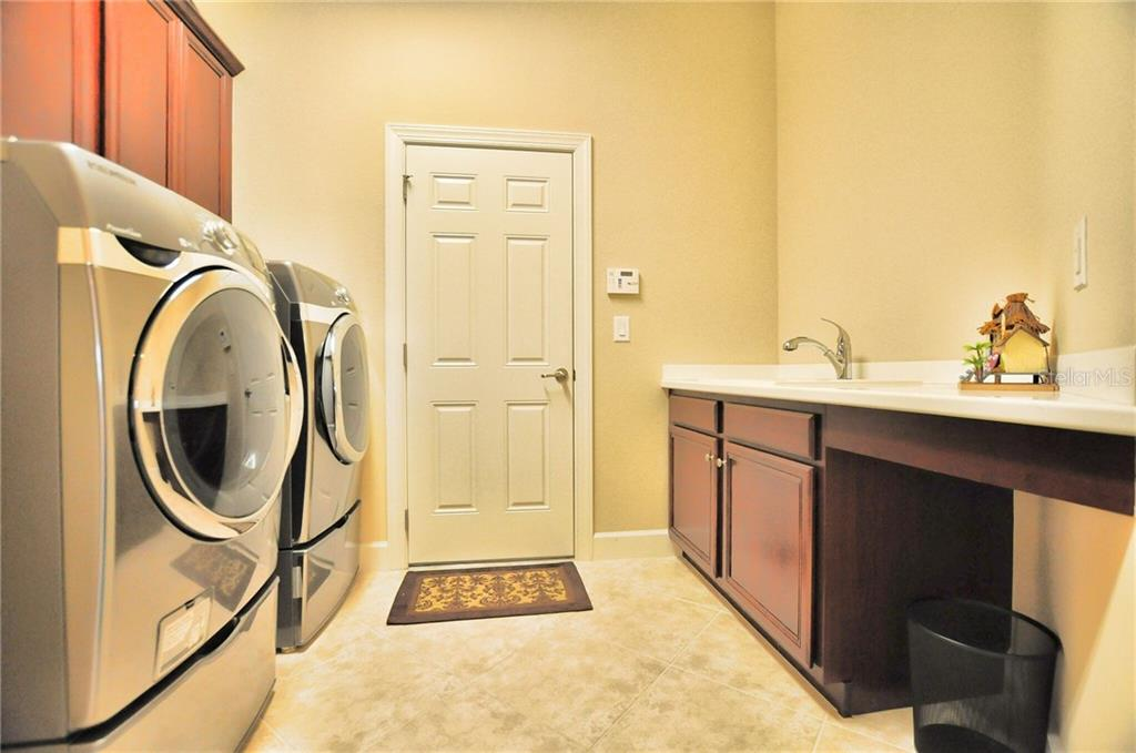 Laundry Room with superior wash and dryer, folding area/sink with additional storage and cabinetry, that leads to 2-1/2 car garage. - Single Family Home for sale at 2839 Mill Creek Rd, Port Charlotte, FL 33953 - MLS Number is C7238545