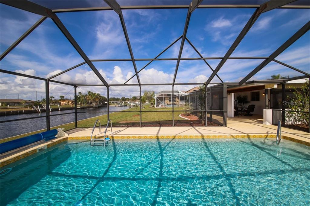 A waterside newly refinished pool is ready for relaxing fun. - Single Family Home for sale at 126 Bangsberg Rd Se, Port Charlotte, FL 33952 - MLS Number is C7409866
