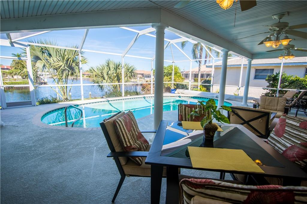 The covered lanai provides shade on the sunniest of Florida days, and yet there's plenty of room to stretch out under the sun in this large screened-in lanai. - Single Family Home for sale at 1440 Appian Dr, Punta Gorda, FL 33950 - MLS Number is C7425399