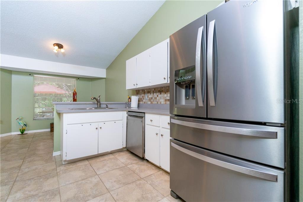 Fabulous frig & large stainless sink overlooking the Lanai & backyard. - Single Family Home for sale at 23374 Macdougall Ave, Port Charlotte, FL 33980 - MLS Number is C7430508