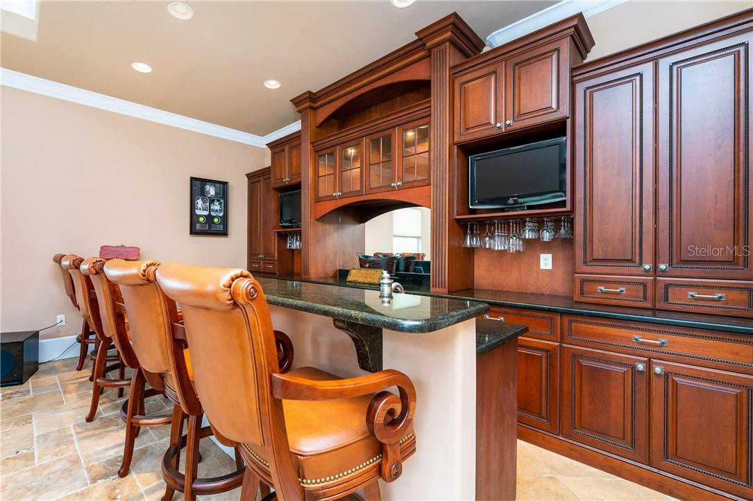 The exceptional great room with a complete bar boasting custom wood cabinetry, granite counters, wine cooler, and built-in stereo cabinet. - Single Family Home for sale at 7440 Riverside Dr, Punta Gorda, FL 33982 - MLS Number is C7436263