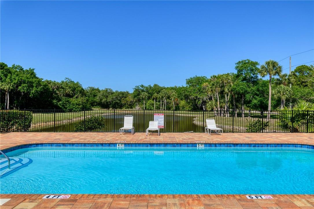 The community swimming pool overlooking a lake, provides a relaxed environment to enjoy the Florida sun. - Single Family Home for sale at 2082 Apian Way, Port Charlotte, FL 33953 - MLS Number is C7441465