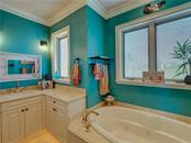 Master Bathroom features walk-in shower and separate whirlpool tub. - Single Family Home for sale at 6150 Manasota Key Rd, Englewood, FL 34223 - MLS Number is C7415176