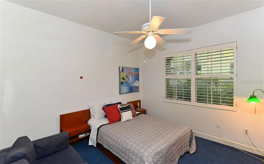 Second bedroom with walk-in closet and plantation shutters - Single Family Home for sale at 924 Indian Beach Dr, Sarasota, FL 34234 - MLS Number is A4179213