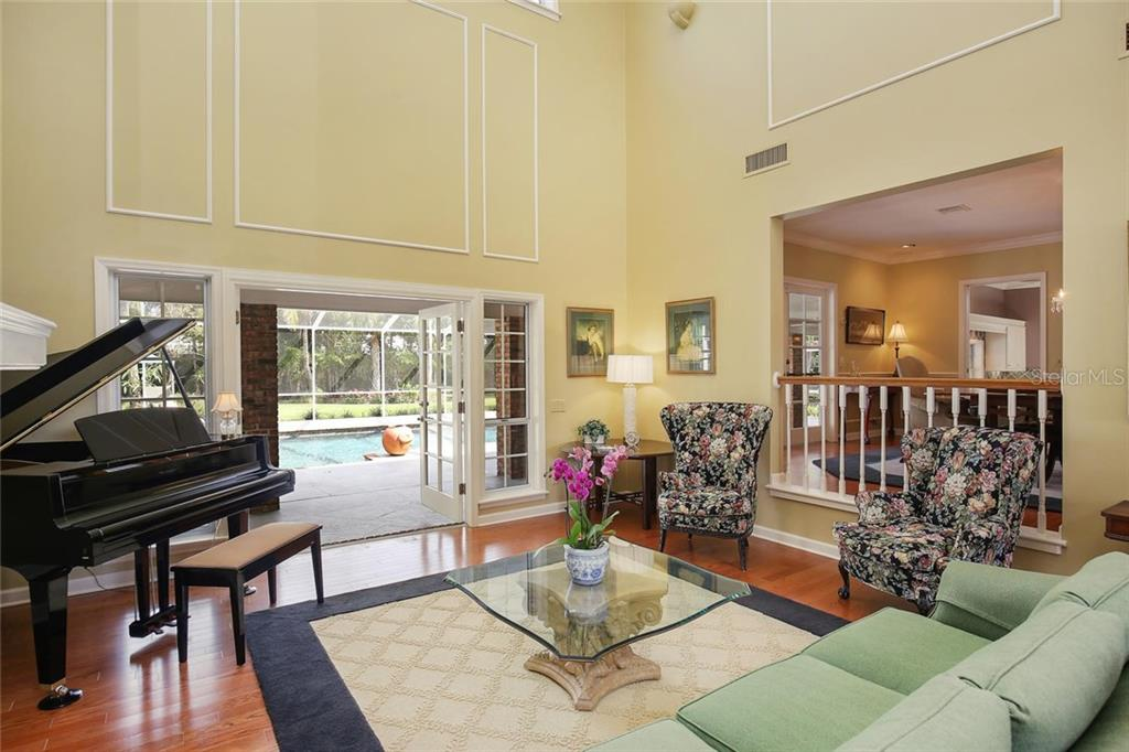 Gorgeous double doors welcome the living room to the screened and covered lanai.  Real hard wood floors, vaulted ceilings and large transom windows make this space feel welcoming and spacious. - Single Family Home for sale at 3765 Beneva Oaks Blvd, Sarasota, FL 34238 - MLS Number is A4185879