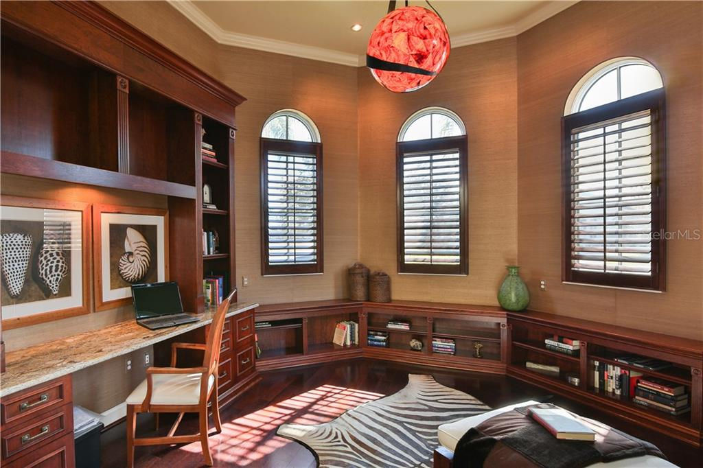 The well appointed office with handsome finishes, plantation shutters, wood floor.  A quiet respite for the end of a busy day. - Single Family Home for sale at 8365 Catamaran Cir, Lakewood Ranch, FL 34202 - MLS Number is A4187448