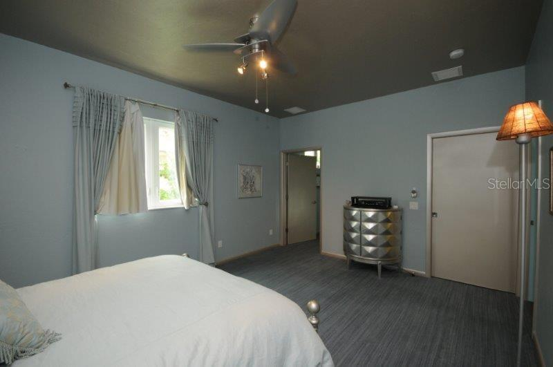 Master bedroom features light-blocking drapes, remote control fan, and walk-in closet. - Single Family Home for sale at 3319 Mayflower St, Sarasota, FL 34231 - MLS Number is A4189488
