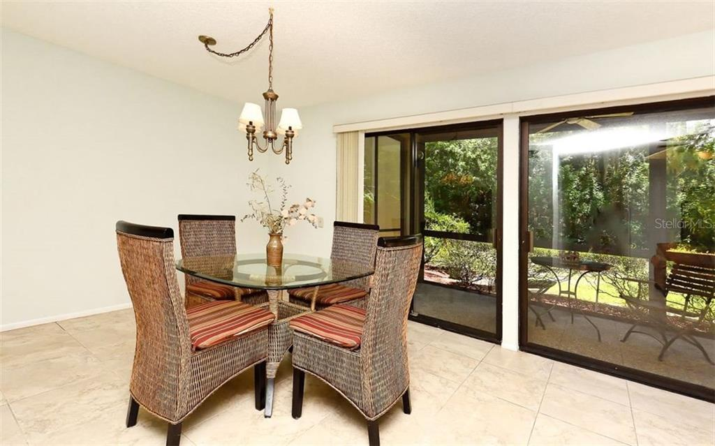 Dining area & wide screened lanai - Condo for sale at 104 Woodland Pl #104, Osprey, FL 34229 - MLS Number is A4190676