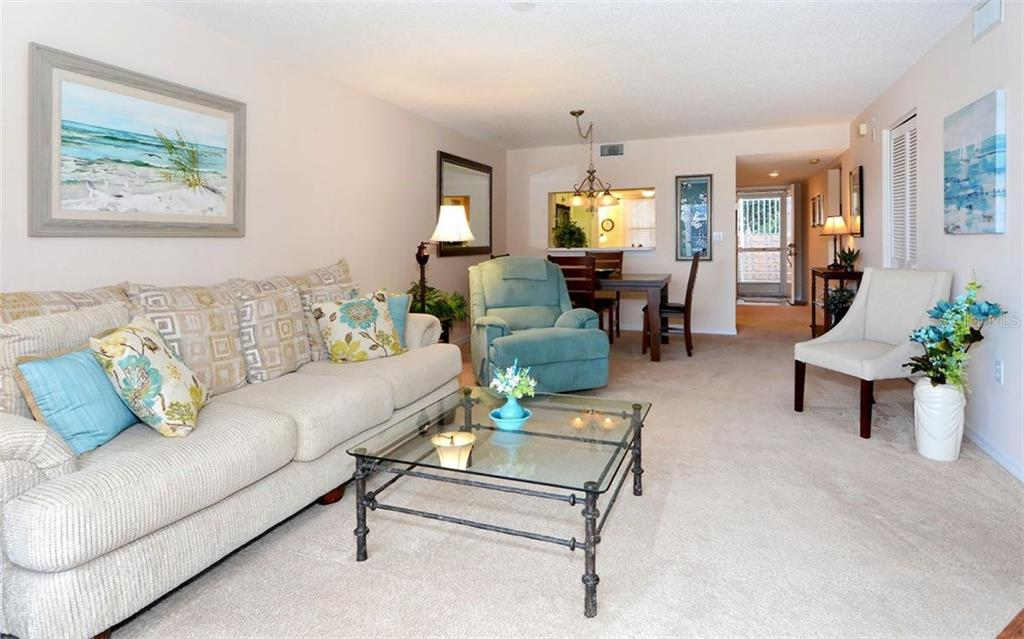 View from the living room. Front entrance on the far right.  Pass thru from kitchen has a breakfast bar. - Condo for sale at 9300 Clubside Cir #1201, Sarasota, FL 34238 - MLS Number is A4192821