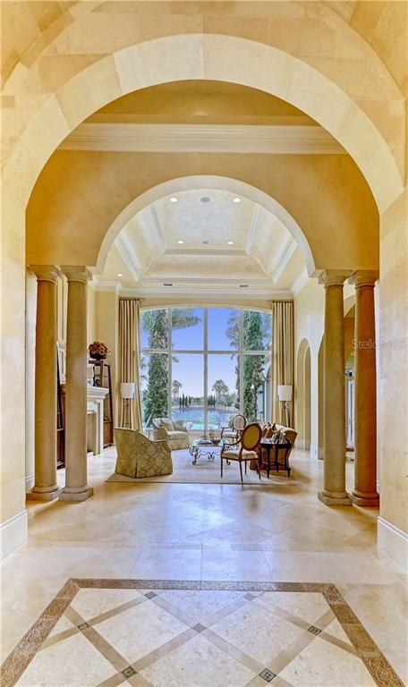 Barrel vaulted entry toward living room with 19 ft faux paneled plaster walls and mud set Jerusalem stone floors - Single Family Home for sale at 16014 Foremast Pl, Lakewood Ranch, FL 34202 - MLS Number is A4194540