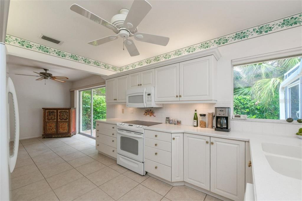 Kitchen with sliders to lanai - Single Family Home for sale at 5515 Contento Dr, Sarasota, FL 34242 - MLS Number is A4194719