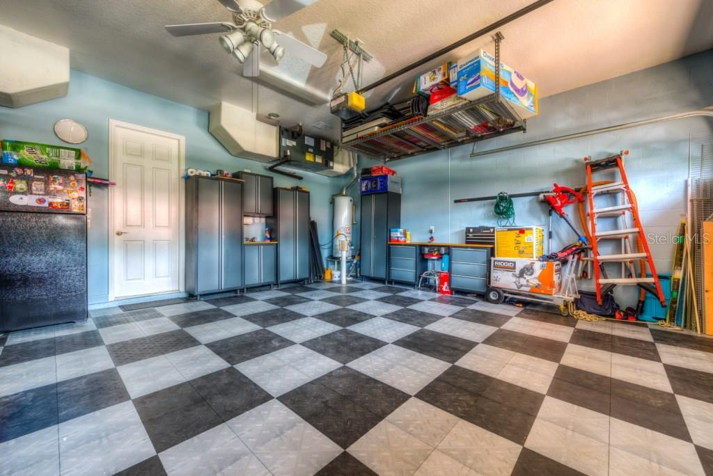 Three car garage to keep your vehicles looking new. Durable non slip rubber mat floor. Note the two celling mounted a/c handlers one 2017 & the other 2012, out of the way and easily serviceable. Smart storage rack and the metal garage cabinets and 2nd refrigerator convey. - Single Family Home for sale at 4965 Gardiners Bay Cir, Sarasota, FL 34238 - MLS Number is A4195176