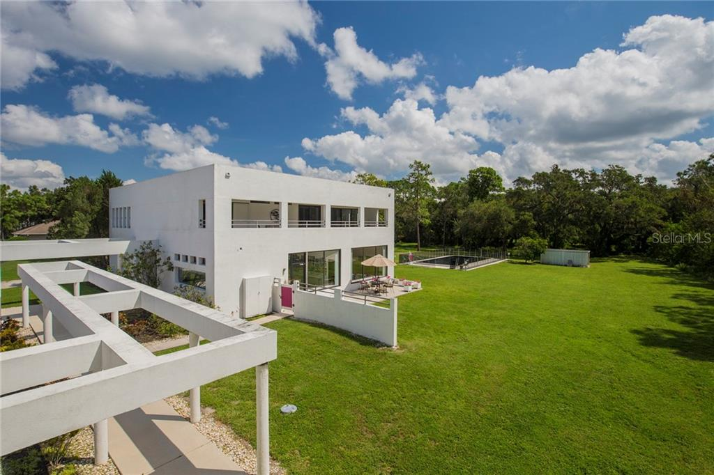 View of the right side of the house and its expansive terrace, great for entertaining or dining. - Single Family Home for sale at 4831 Hoyer Dr, Sarasota, FL 34241 - MLS Number is A4195351