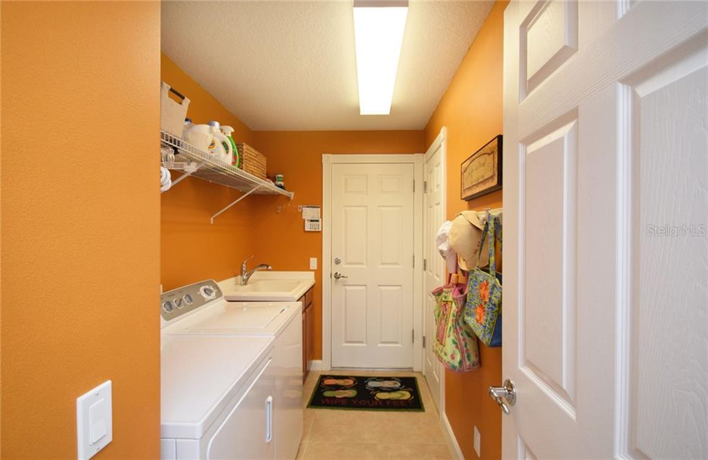 Laundry Room has a utility sink, leads to the 2-car garage - Villa for sale at 2127 Burgos Dr, Sarasota, FL 34238 - MLS Number is A4195921
