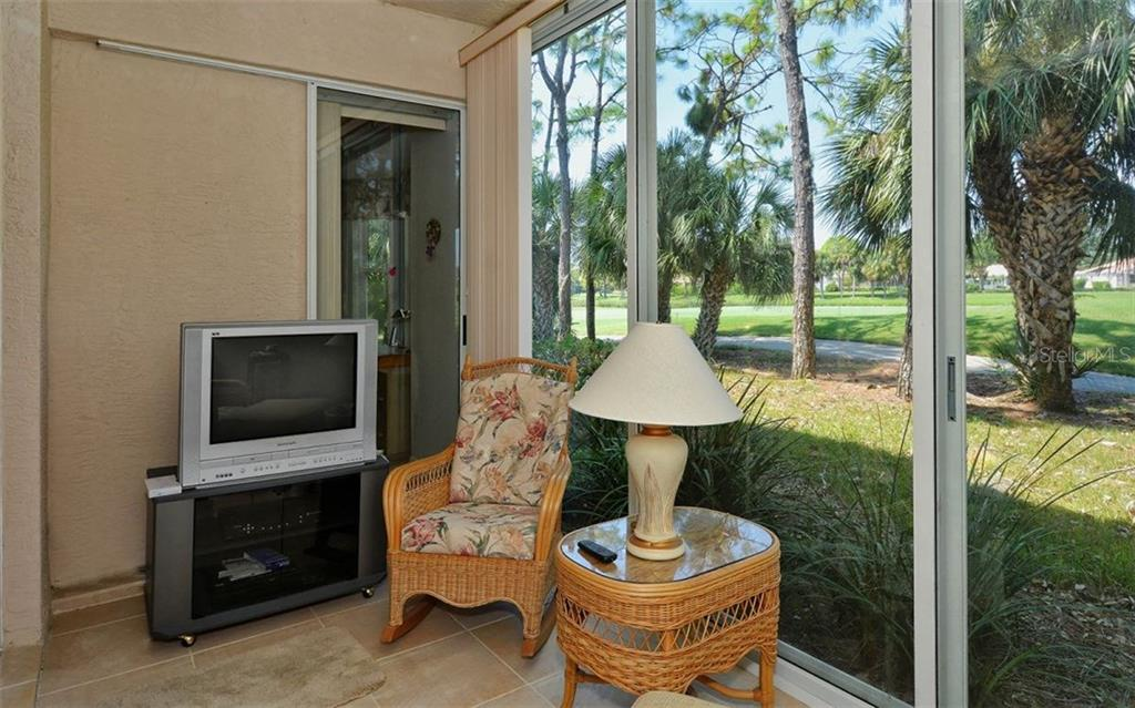 Glass and screen enclosed lanai. Tree-lined view of the 17th fairway. - Condo for sale at 9570 High Gate Dr #1712, Sarasota, FL 34238 - MLS Number is A4196327
