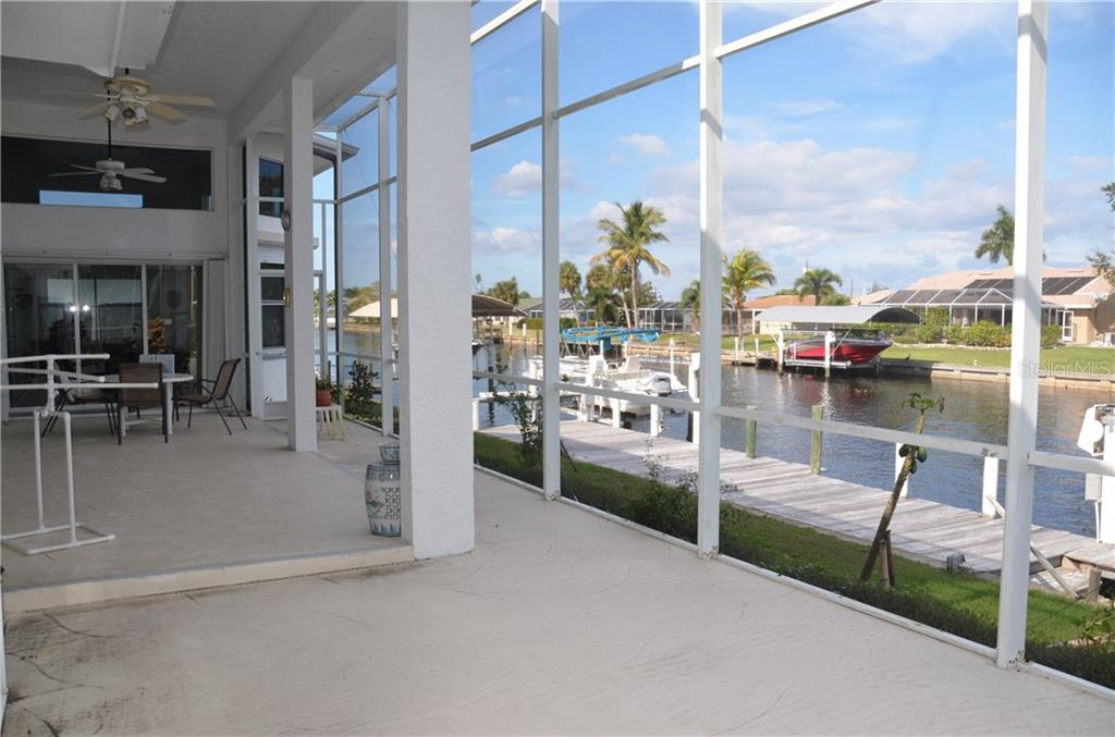 View of the canal from lanai to show sliders off kitchen that step out to spacious patio area-a great place to entertain guests or relax with your morning coffee. - Single Family Home for sale at 140 Sinclair St Se, Port Charlotte, FL 33952 - MLS Number is A4204644