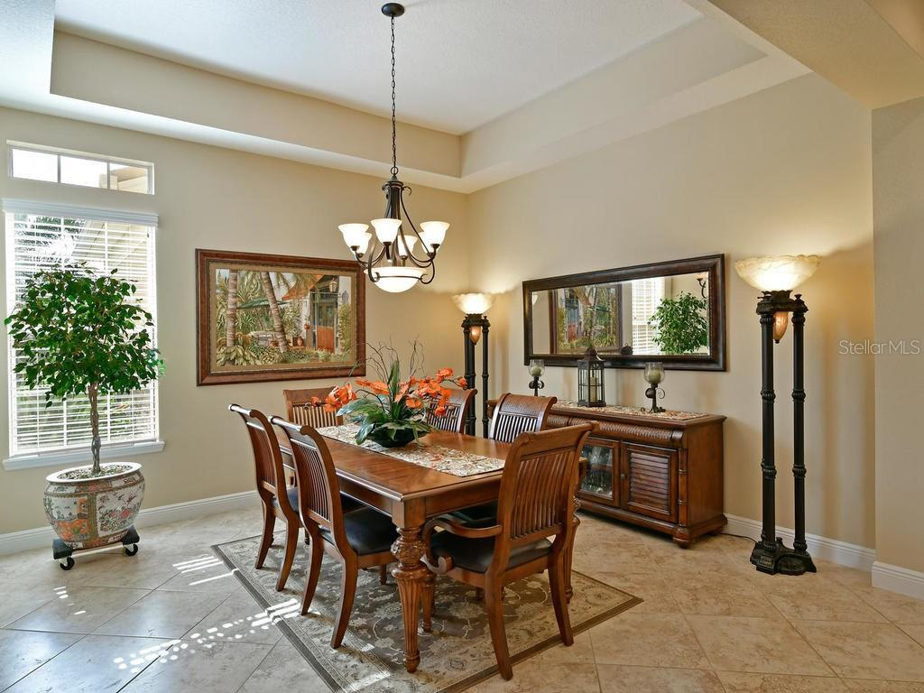 Spacious tray ceilings, warm colored tile, and transom top windows add light and warmth to the formal dining room - Single Family Home for sale at 6601 Horned Owl Pl, Sarasota, FL 34241 - MLS Number is A4205612