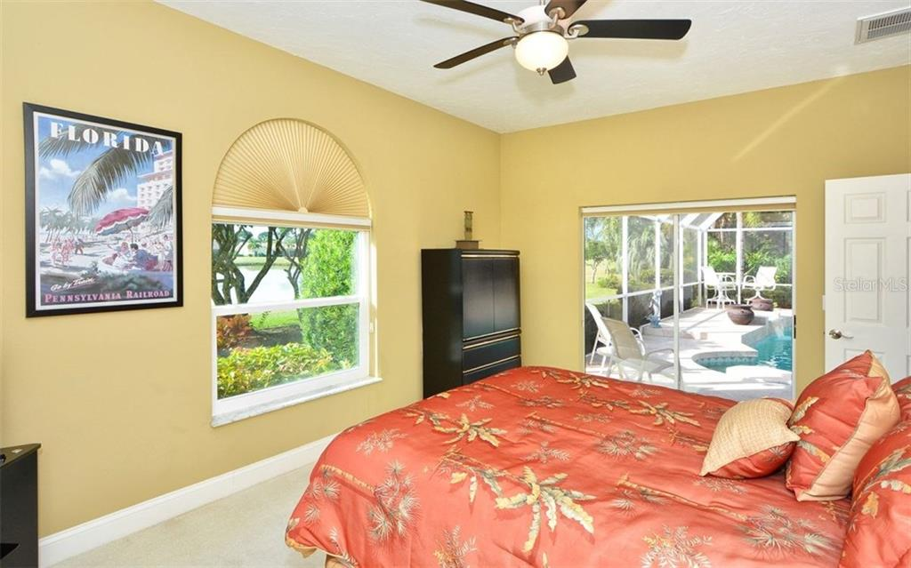 Bedroom # 2 with sliders to pool and overlooks lake and golf course - Single Family Home for sale at 3882 Spyglass Hill Rd, Sarasota, FL 34238 - MLS Number is A4206477