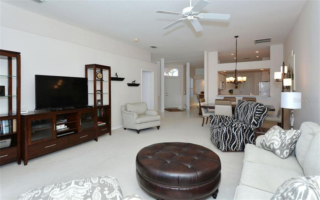 Another view of the spacious living area.  Kitchen has a breakfast bar and large pass-thru to the dining room. - Villa for sale at 9554 Forest Hills Cir, Sarasota, FL 34238 - MLS Number is A4206506