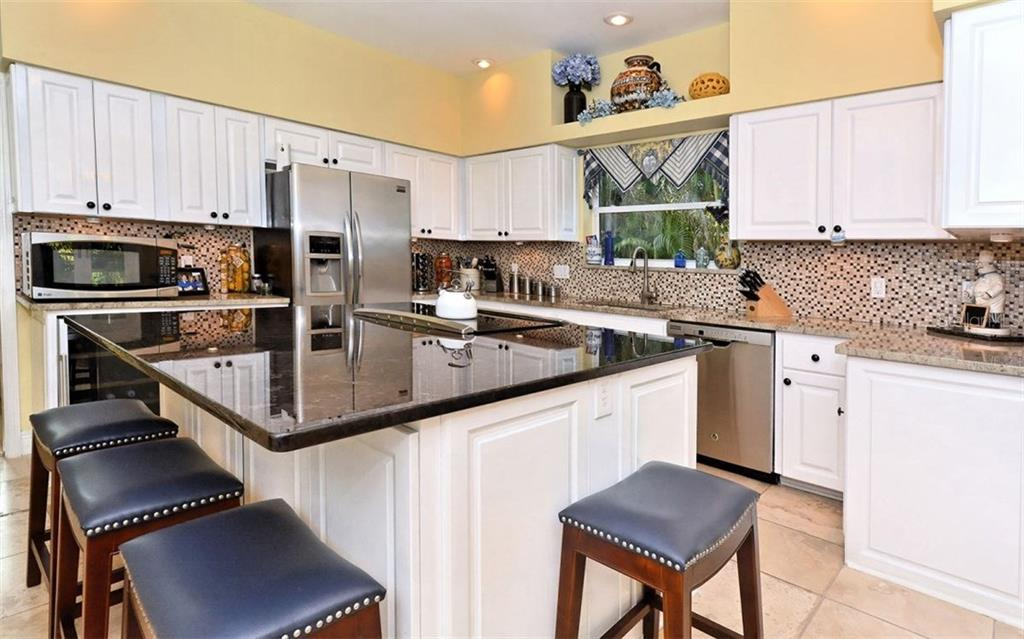 Kitchen with breakfast counter on center island - Single Family Home for sale at 141 Ogden St, Sarasota, FL 34242 - MLS Number is A4208039