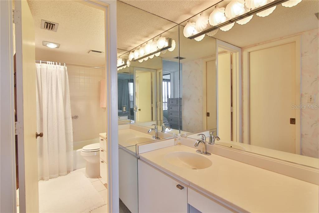 Master bath with dual vanities and walk in closet with pocket door. - Single Family Home for sale at 5790 Midnight Pass Rd #704, Sarasota, FL 34242 - MLS Number is A4208095