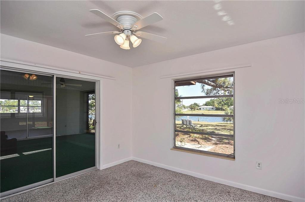 Bedroom 2 with sliders to covered lanai and canal views - Single Family Home for sale at 1953 Fairview Dr, Englewood, FL 34223 - MLS Number is A4213338