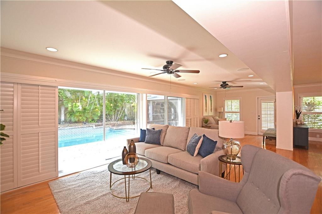 Living area with view of pool and tropical landscaping beyond. - Single Family Home for sale at 1670 Bay View Dr, Sarasota, FL 34239 - MLS Number is A4400079